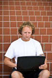 Chating outdoors. Young guy sitting in the starway using laptop computer royalty free stock photography
