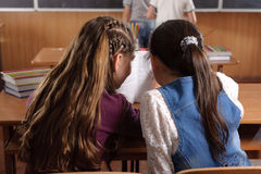 Chating at school. Two schoolgirls chating in classromm during lesson royalty free stock images