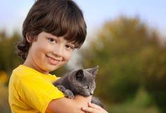 Chaton sur le bras du garçon dehors, enfant énorme son animal familier d'amour Photos libres de droits