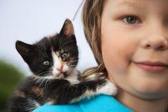 Chaton sur le bras du garçon dehors, enfant énorme son animal familier d'amour Image libre de droits