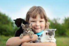 Chaton sur le bras du garçon dehors, enfant énorme son animal familier d'amour Images libres de droits