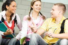 Chatting. Image of three attractive students chatting before lesson stock photography