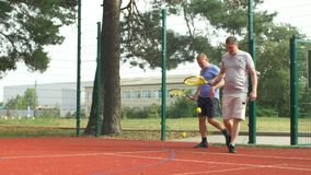 Chatting active sporty men going to tennis court