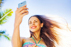 Chatting at the beach. Young pretty woman using her phone on the beach Stock Image
