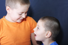 Chatting brothers. Two brothers chatting closeup photo against blue background Stock Photos