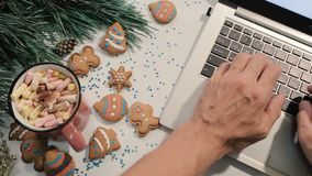 Chatting during Christmas and New Year holidays. Unrecognizable man typing on laptop near festive decorated pine, cookies and cup of marshmallows, top view stock video footage