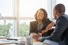 Chatting with colleague. Beautiful smiling African-American business lady chatting with coworker royalty free stock images
