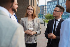 Chatting with Colleagues Outdoors. Multi-ethnic group of colleagues standing at office building and chatting animatedly with each other while having coffee break royalty free stock photo