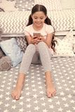Chatting with friend. Girl child sit on bed with smartphone in bedroom. Kid prepare to go to bed. Girl kid long hair. Cute pajamas relax send message wish sweet stock photography