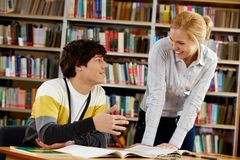 Chatting friends. Portrait of clever students chatting while preparing lessons in college library royalty free stock images