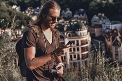 Chatting with friends. Young man in casual clothing using smart phone and smiling while standing on the hill outdoors royalty free stock photography