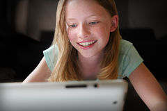 Chatting with friends online. Teenage girl with Tablet computer, chatting, smiling stock image