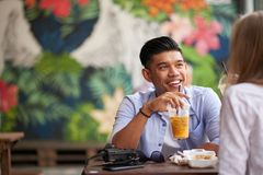 Chatting with girlfriend. Cheerful Asian men chatting with his Caucasian girlfriend at cafe Royalty Free Stock Images