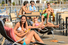Chatting girls lying on deckchair sunbathing Stock Image