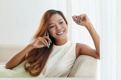 Chatting on phone. Cheerful young Filipino woman sitting on sofa and chatting on phone Royalty Free Stock Photo