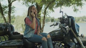 Chatting on phone cute girl sitting on motorbike. Stunning motorbiker girl with long hair chatting on smartphone while sitting on motorcycle in summer nature stock footage