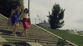 Women with shopping bags walking down the stairs stock footage