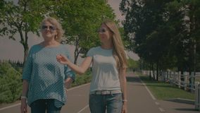 Free Chatting Senior Mother And Adult Daughter Walking In Park Stock Photography - 122522422