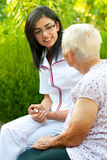 Chatting with sick elderly woman. A young doctor / nurse visiting an elderly sick women and chatting with her outdoors royalty free stock photography