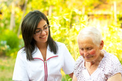 Chatting with sick elderly woman. A young doctor / nurse visiting an elderly sick women and chatting with her outdoors royalty free stock images
