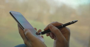 Chatting on smart phone during train ride. Close-up shot of a girl texting with pen on smart phone in train. Nature scenes passing in background stock video