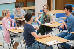 Chatting students in the classroom. Students sitting in a classroom and talking while having fun Stock Photo
