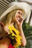 Chatting In The Sunshine. A beautiful young woman bathed in sunshine and making a call on her cell phone Stock Image