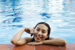 Chatting at Swimming Pool. Asian woman making a phone call at swimming pool Royalty Free Stock Images