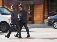 Chatting Whilst Crossing för två affärsman gata Arkivbilder