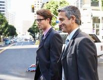 Chatting Whilst Crossing för två affärsman gata Arkivfoto
