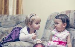 Chattingl de deux petites filles sur un sofa Images stock