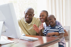chattting与计算机的愉快的微笑的家庭 库存照片