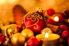 Or chaud et fond rouge de lueur d'une bougie de Noël Photos libres de droits