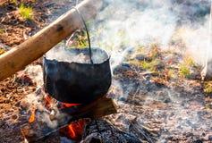 Chaudron en vapeur et fumée sur le feu ouvert Images stock