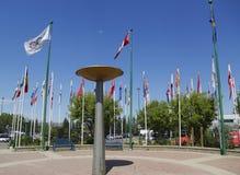 Chaudron olympique et drapeaux internationaux en parc olympique de Canada à Calgary Image libre de droits