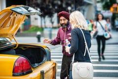 Chaufför för New York City taxitaxi som upp väljer passanger från gatan Royaltyfri Bild
