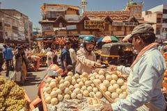 Chaufför i hjälm som köper nya frukter och apelsiner på utomhus- marknadsplats med många kunder på den upptagna asiatiska gatan Royaltyfri Fotografi