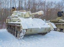 Chaufför-mekanikern rengöringarna snöar från behållaren su-76 Royaltyfri Foto