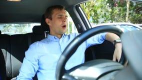 Chauffören av mannen avverkar sovande i platsen för chaufför` s på sidan av den upptagna vägen Vänta i bilen stock video