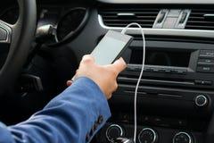 Chauffören av medlet, håll i hans hand som telefonen förband vid en vit tråd, till bilmusiksystemet arkivfoton
