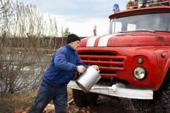 Chauffören av vattnet tvättar den gamla brandlastbilen Fotografering för Bildbyråer
