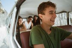 Chauffören för den unga mannen tycker om en tur med leende för att gå till stranden arkivfoton