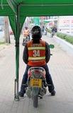 Chauffören i orange waistcoat sitter på hans motorcykeltaxi som väntar på passageraren royaltyfri fotografi