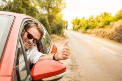 Chauffören i tummar för en bilvisning gör en gest upp arkivbild