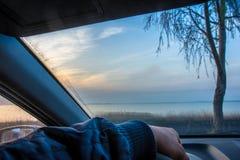 Chauffören sitter i bilen och ser ut fönstret Han körde upp till sjön på solnedgången eller soluppgång royaltyfria bilder