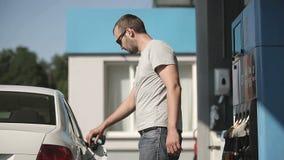 Chauffören som pumpar bensin på bensinstationen arkivfilmer