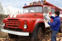 Chauffören tvättar den gamla brandlastbilen Royaltyfria Bilder