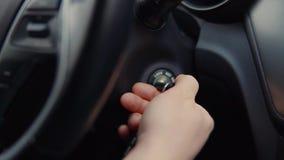 Chauffören vänder tändningtangenten i bil, närbild av handen stock video