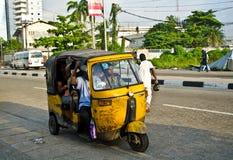 Chaufförer av gula tuktuks ply deras handel runt om hamnstaden Royaltyfria Bilder