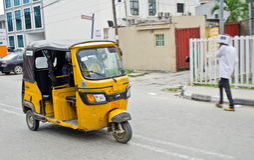 Chaufförer av gula tuktuks ply deras handel runt om hamnstaden Royaltyfri Foto